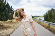 Smiling woman on rural road at the lakeside - BSZF01426