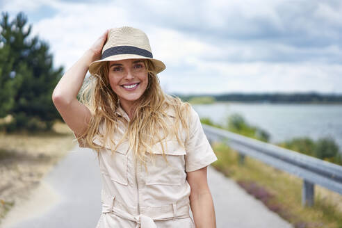 Portrait of smiling woman on rural road at the lakeside - BSZF01432