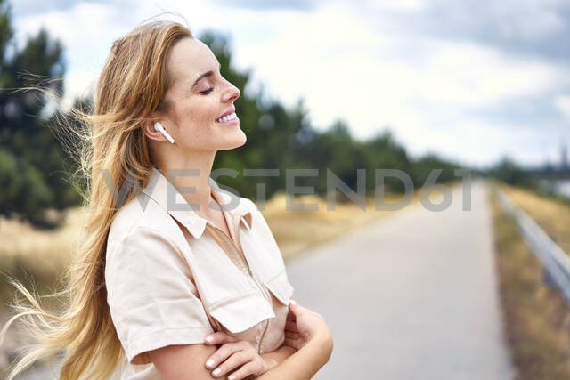 Smiling woman with wireless earphones and closed eyes in nature - BSZF01435 - Bartek Szewczyk/Westend61