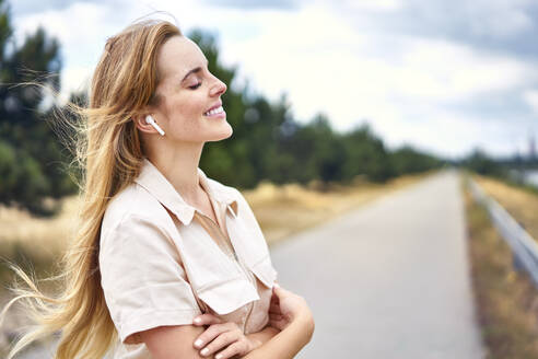 Smiling woman with wireless earphones and closed eyes in nature - BSZF01435