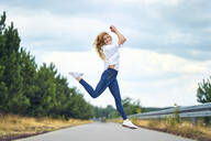 Cheerful woman jumping on rural road - BSZF01438