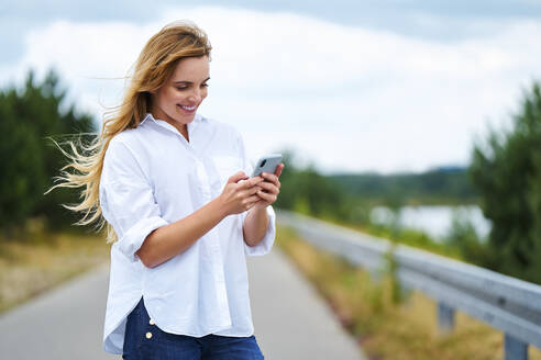 Happy woman checking cell phone on rural road - BSZF01441