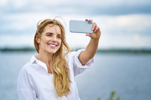 Happy woman taking selfie with smartphone at the lakeside - BSZF01444