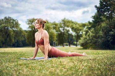 Woman doing cobra pose during yoga training in the park - BSZF01450