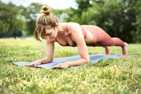 Athletic woman doing plank exercises outdoors in the park - BSZF01456