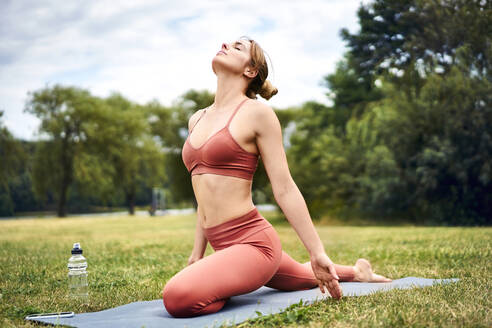 Woman practicing yoga in park - BSZF01459
