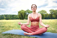 Woman practicing yoga in park meditating - BSZF01462