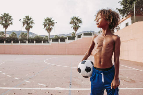 Boy holding a soccer ball standing on a soccer field - LJF00980