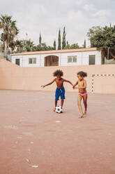 Two children playing soccer on a soccer field - LJF00983