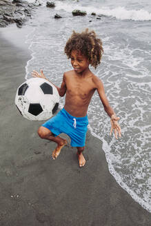 Boy playing with a football on the beach - LJF00986
