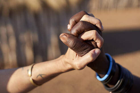 Muhacaona traditional woman and white woman holding hands, Oncocua, Angola - VEGF00639