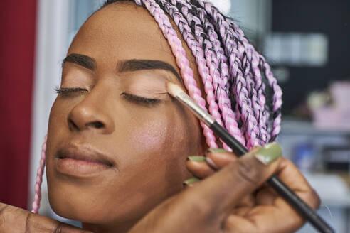 Visagiste applying eyeshadow on young woman's eyelid, close-up - VEGF00664