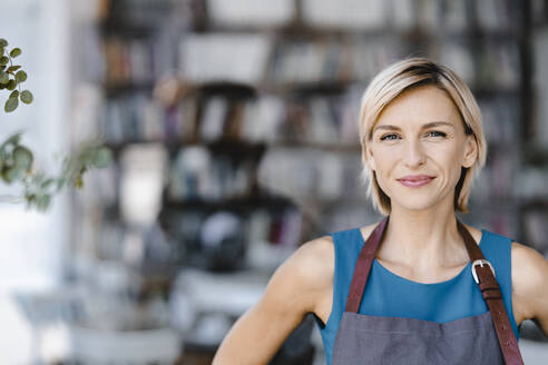 Portrait of blond woman, standing in front of her own coffee shop - KNSF06323