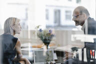 Businessman and woman having a meeting in a coffee shop, discussing work - KNSF06326