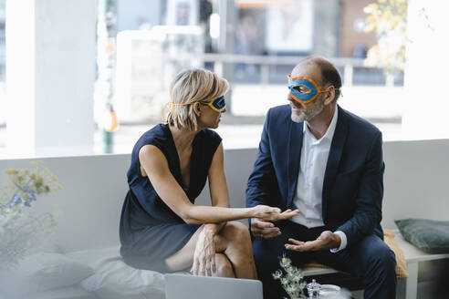 Businessman and woman wearing super hero masks, trying to find solutions - KNSF06338
