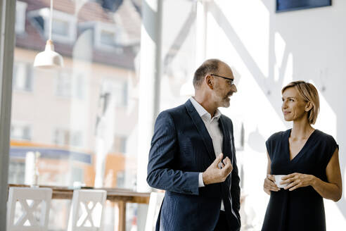 Businessman and woman talking about solutions, drinking coffee - KNSF06353