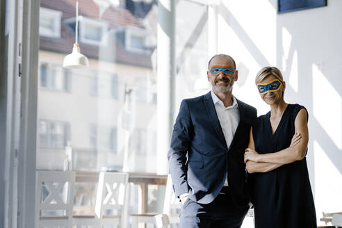 Businessman and woman wearing super hero masks, standing in coffee shop - KNSF06359