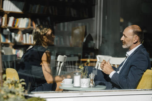 Businessman and woman having a meeting in a coffee shop - KNSF06368
