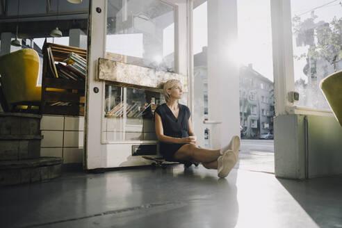 Businesswoman in coffee shop, sitting on skateboard, relaxing - KNSF06377