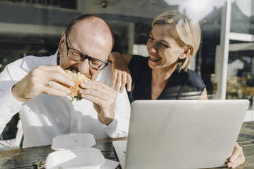 Businessman eating hamburger in coffee shop, while colleague is using laptop - KNSF06380