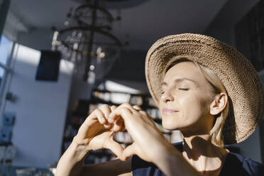Woman with straw hat, looking into the sun, making heart shaped finger frame - KNSF06383