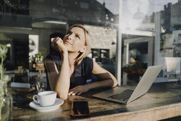 Blond woman using laptop in a coffee shop - KNSF06386