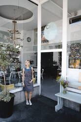 Woman with apron standing in front of coffee shop, - KNSF06407