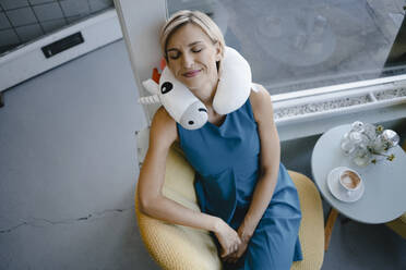 Smiling woman sitting in chair, taking a nap with unicorn pillow  around her neck - KNSF06410