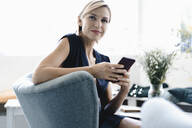 Businesswoman sitting in coffee shop,using smartphone - KNSF06419