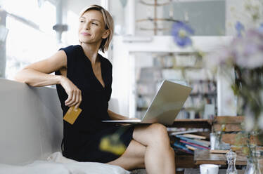 Businesswoman making online payment, sitting in coffee shop, using laptop and credit card - KNSF06422