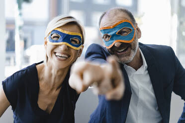 Businessman and woman wearing super hero masks, pointing at camera - KNSF06428
