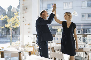 Successful businessman and woman high-fiving in a coffee shop - KNSF06434