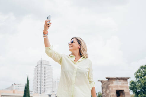 Senior woman taking photos with a smartphone in the city - OCMF00705