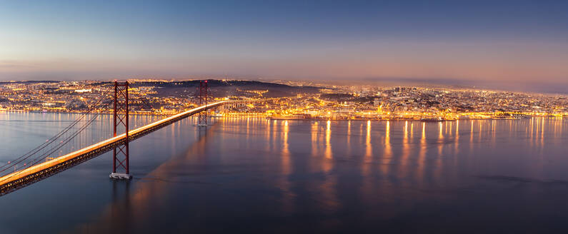 April 25th Bridge over Tagus river against illuminated cityscape at dusk, Lisbon, Portugal - XCF00199