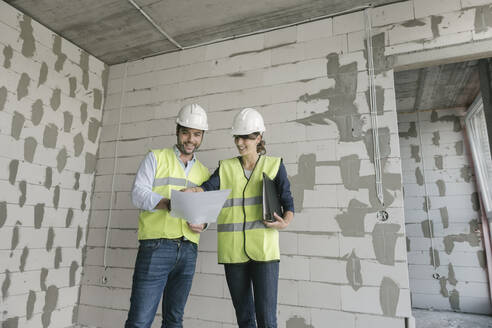 Lithuania, Vilnius, two architects checking architectural plan while standing at construction site - AHSF00806