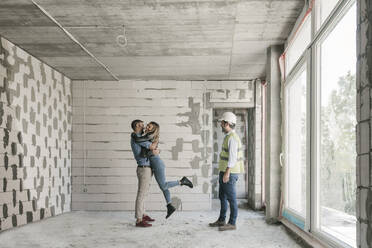 Architect having a meeting with happy future owners on construction site - AHSF00818