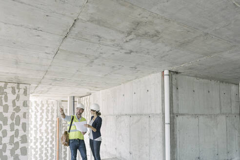 Male architect and female manager talking about architectural plan at construction site - AHSF00821
