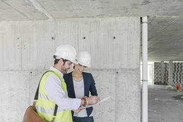 Architect and female manager talking about architectural plan at construction site - AHSF00824