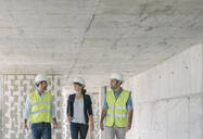 Male architects and female manager talking while walking at construction site - AHSF00830