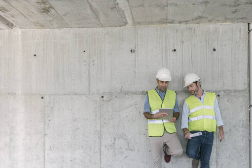 Two workers using tablet on construction site - AHSF00833