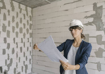 Female architect checking architectural plan on construction site - AHSF00839