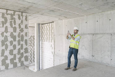 Architect taking a photo on construction site - AHSF00842