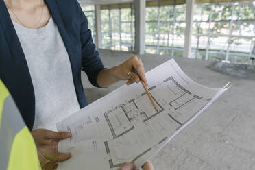 Male architect and female manager talking about architectural plan at construction site - AHSF00845