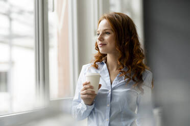 Portrait of redheaded businesswoman with coffee to go looking out of window - KNSF06436