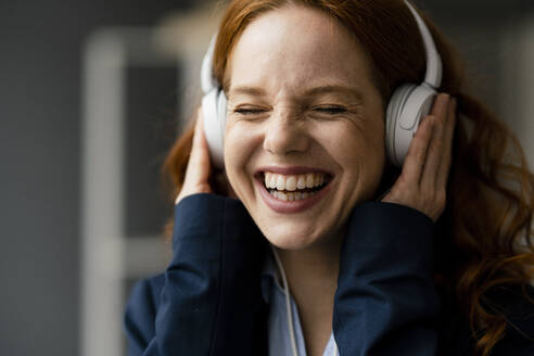 Portrait of laughing redheaded businesswoman listening music with white headphones - KNSF06439
