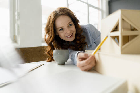 Portrait of smiling redheaded woman looking at architectural model - KNSF06442