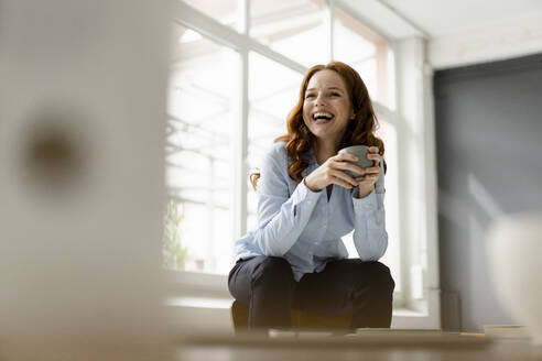 Portrait of laughing redheaded woman with tea bowl sitting on backrest in a loft - KNSF06445