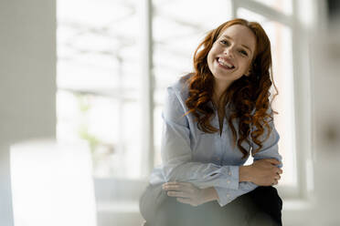Portrait of laughing redheaded woman sitting in a loft - KNSF06448