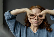 Portrait of redheaded woman shaping glasses with fingers - KNSF06463