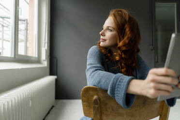Portrait of redheaded woman with digital tablet sitting in a loft looking out of window - KNSF06469